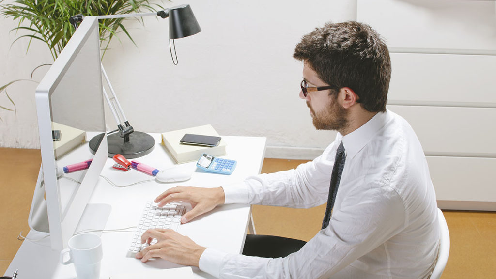 Young businessman typing a computer in office.